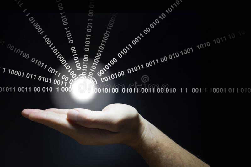 A mão guarda uma bola de incandescência que emite-se dados fotos de stock