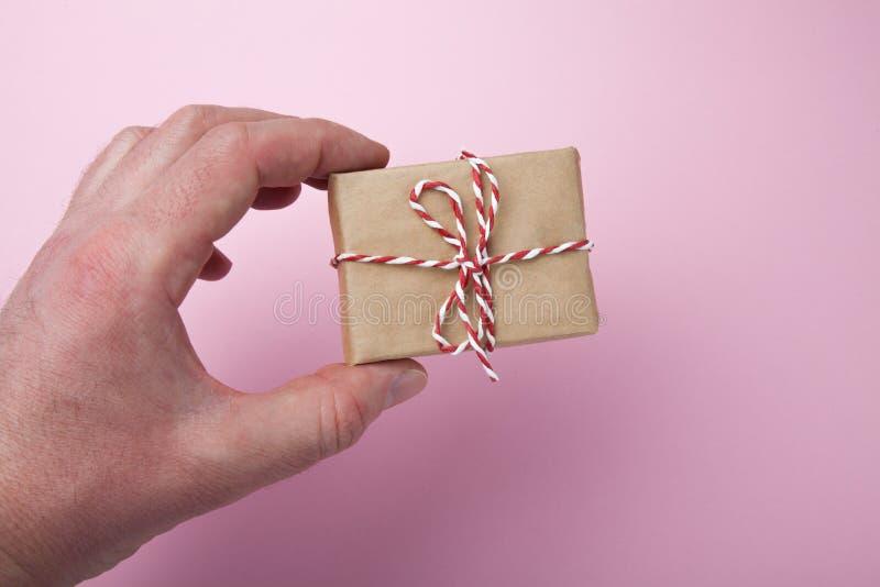 A mão guarda uma caixa de presente caseiro pequena em um fundo cor-de-rosa imagens de stock royalty free