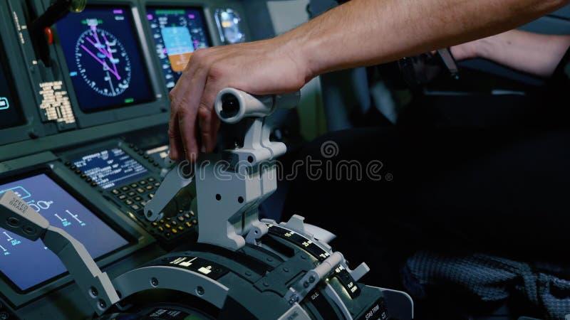 Mão guardando piloto no punho de alavanca da pressão para o controle de motor do avião de passageiros fotografia de stock royalty free