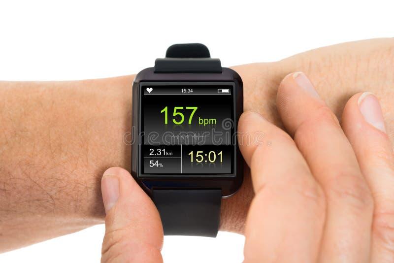 Mão humana com o smartwatch que mostra a taxa da pulsação do coração foto de stock