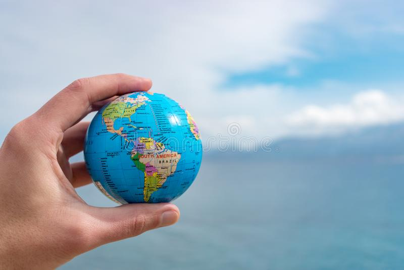 A mão humana está guardando o globo pequeno na frente do céu azul fotos de stock royalty free