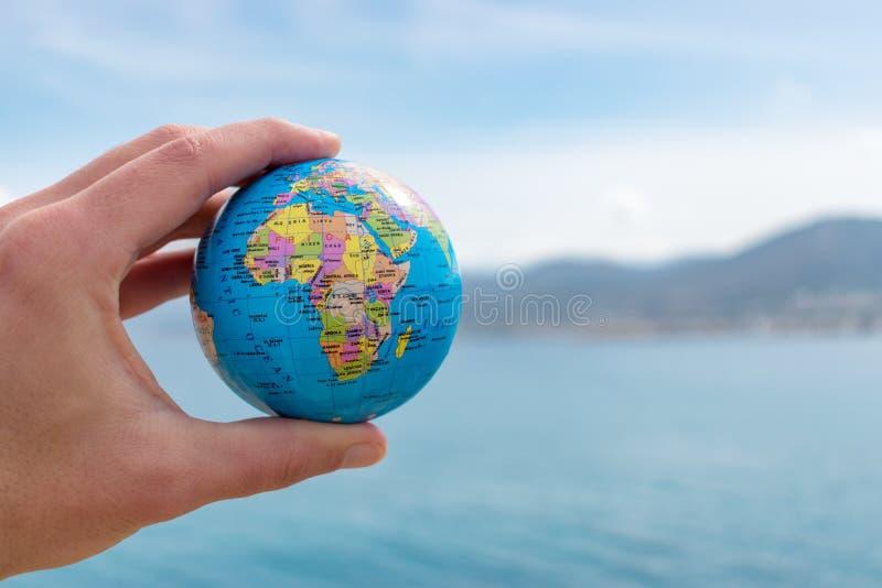 A mão humana está guardando o globo pequeno na frente do céu azul fotos de stock