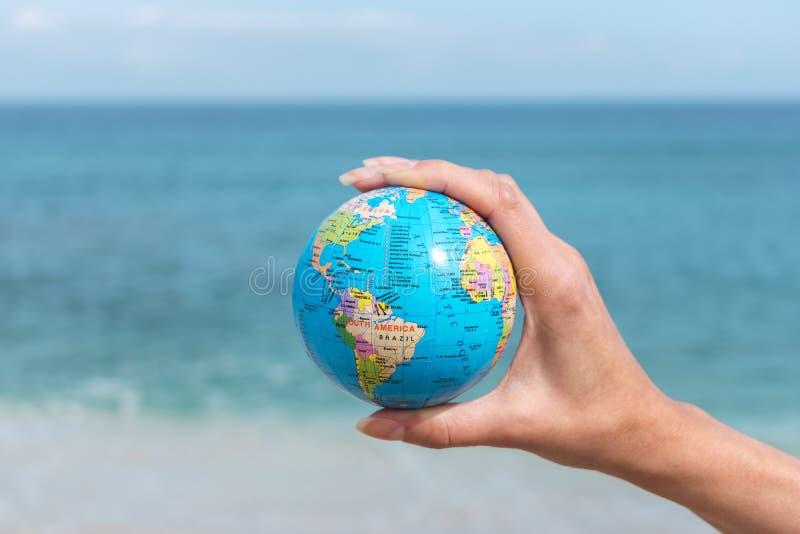 A mão humana está guardando o globo pequeno na frente do mar foto de stock