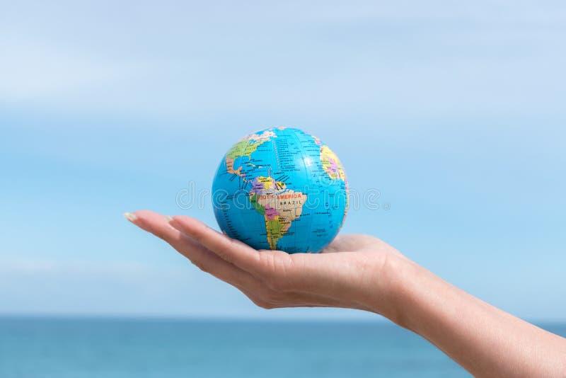 A mão humana está guardando o globo pequeno na frente do mar imagem de stock