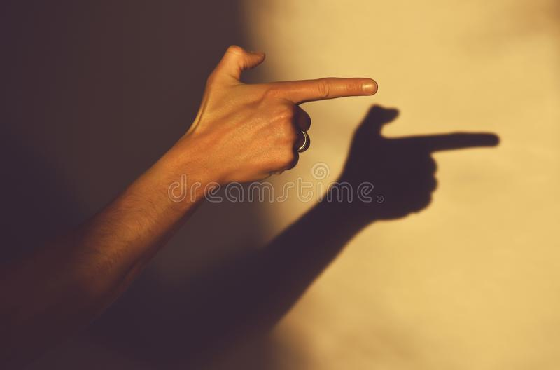 A mão humana indica o sentido que aponta com o indicador, sombra imagem de stock