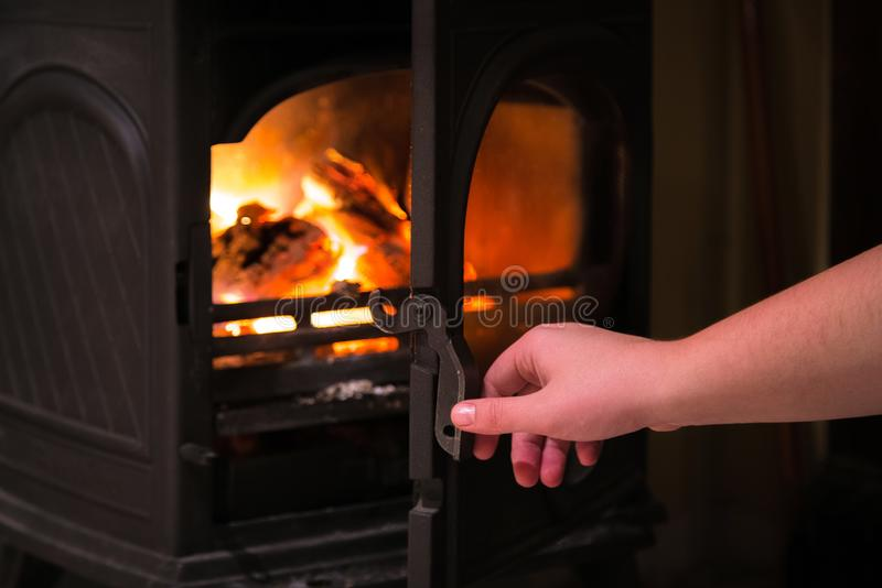 Mão humana que abre uma porta da chaminé ardente com l de madeira fotografia de stock