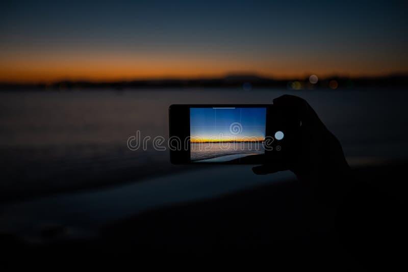 mão humana que guarda um telefone que toma uma imagem de um por do sol imagem de stock royalty free