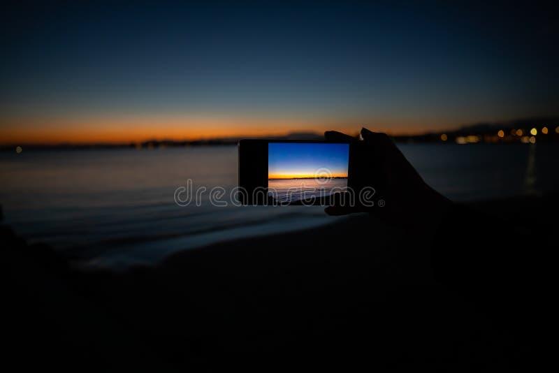 mão humana que guarda um telefone que toma uma imagem de um por do sol fotos de stock royalty free