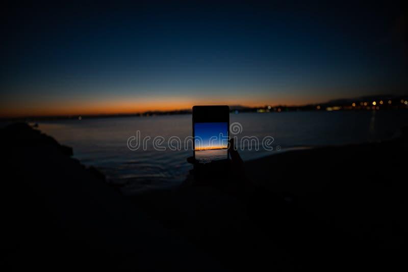 mão humana que guarda um telefone que toma uma imagem de um por do sol imagem de stock