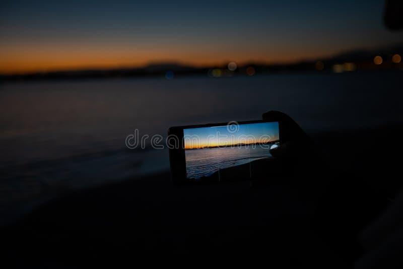 mão humana que guarda um telefone que toma uma imagem de um por do sol fotos de stock