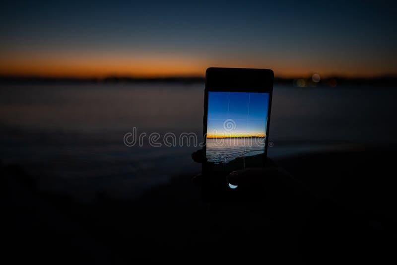 mão humana que guarda um telefone que toma uma imagem de um por do sol foto de stock royalty free