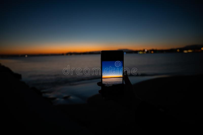 mão humana que guarda um telefone que toma uma imagem de um por do sol imagens de stock royalty free