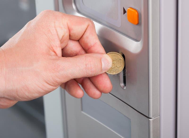 Mão humana que introduz a moeda na máquina de venda automática imagem de stock