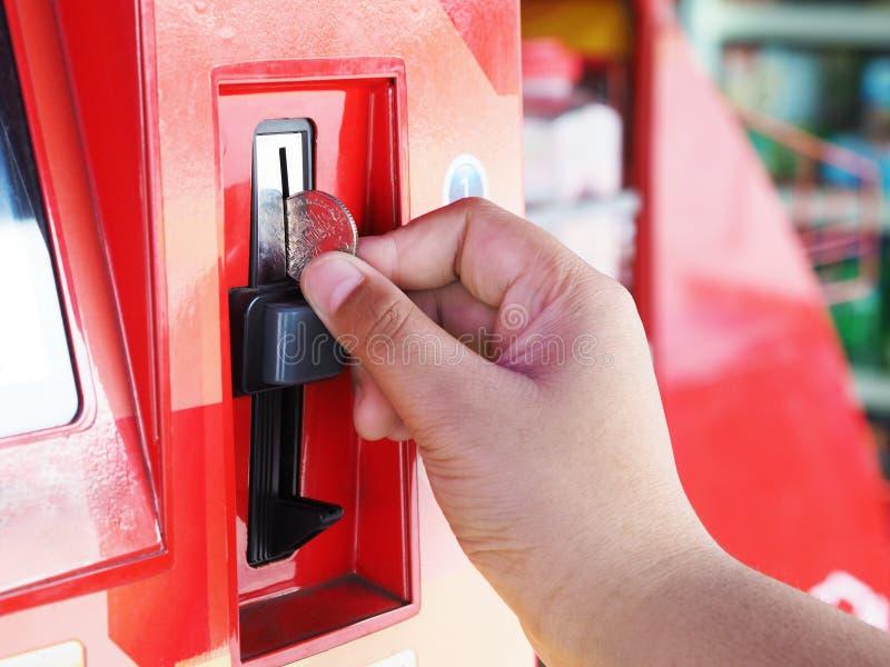 Mão humana que introduz a moeda na máquina de venda automática fotografia de stock royalty free