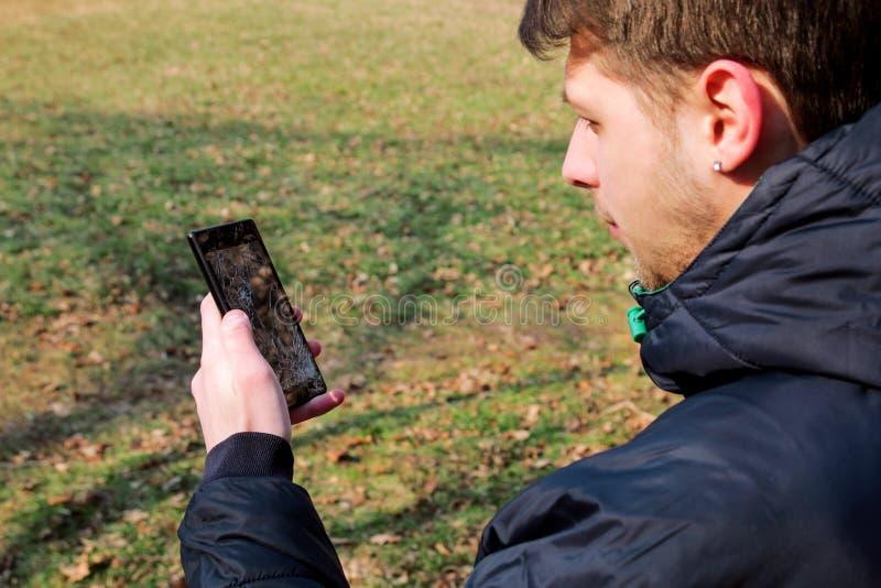 A mão humana que mantém o telefone esperto quebrado rachou a tela danificada foto de stock
