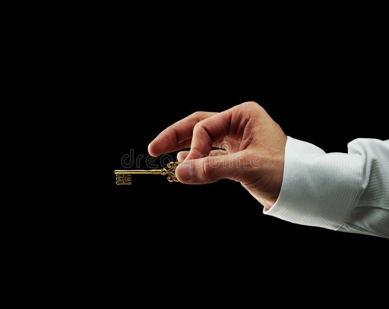 Mão humana que prende a chave dourada fotos de stock royalty free