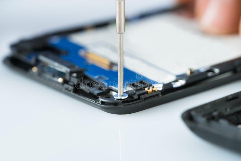 Mão humana que repara o telefone celular com chave de fenda fotografia de stock
