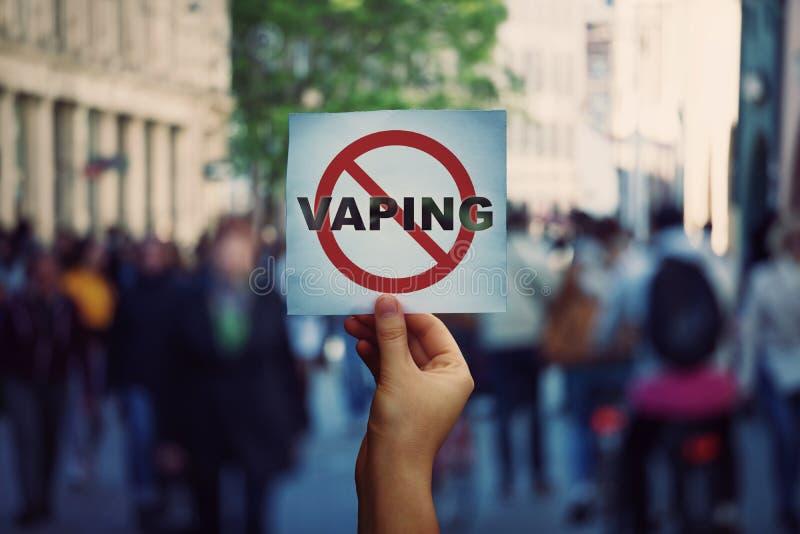Mão humana segurando um cartaz de protesto para parar de vaporizar mensagem sobre um fundo lotado de rua Proibição de vapores aro imagens de stock royalty free