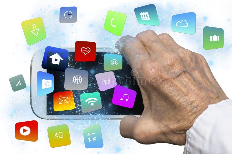 Mão idosa que guarda um smartphone com apps e ícones de flutuação coloridos modernos imagens de stock
