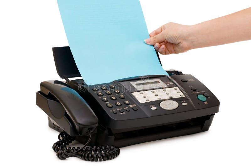 A mão introduz um papel em um fax imagem de stock