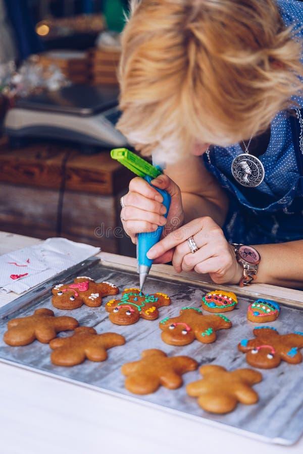 Mão irreconhecível do pasteleiro das mulheres que decora um gingerman com um saco da pastelaria, tirando um sorriso, fazendo o bo fotos de stock