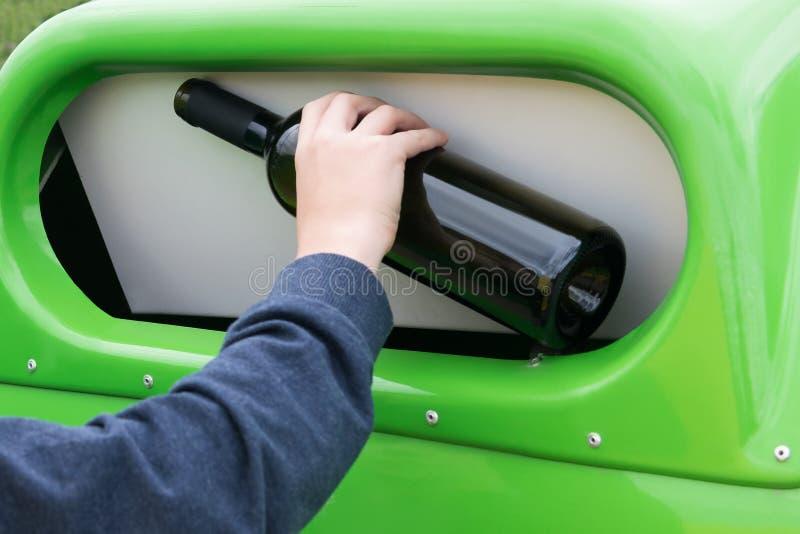 A mão joga a garrafa de vinho vazia no escaninho de lixo verde, close-up fotos de stock