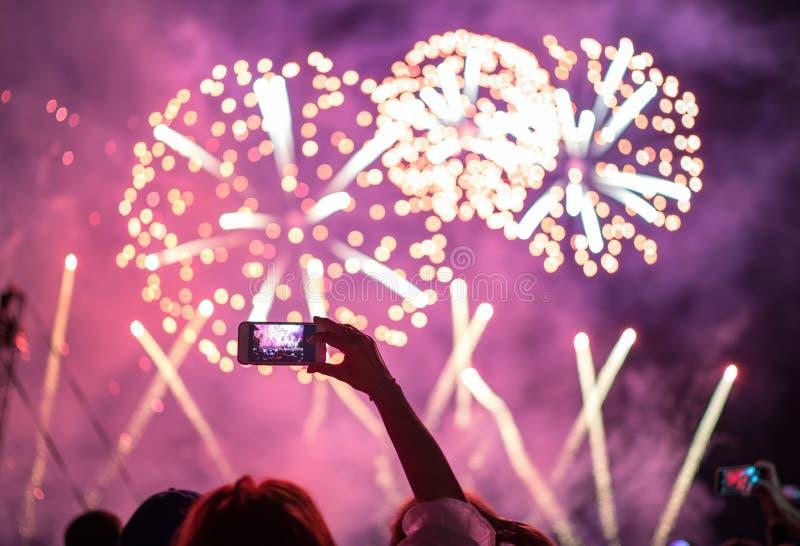 Mão levantada com tiro do smartphone video do céu horizontal dos fogos de artifício da noite Entretenimento brilhante colorido do foto de stock