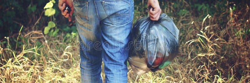 A mão mantém contra uma floresta completa do lixo um grande saco de plástico preto, um dia de verão, recolha de lixo na natureza fotografia de stock