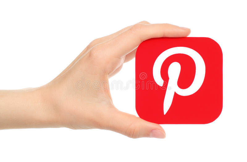 A mão mantém o logotype de Pinterest impresso no papel foto de stock