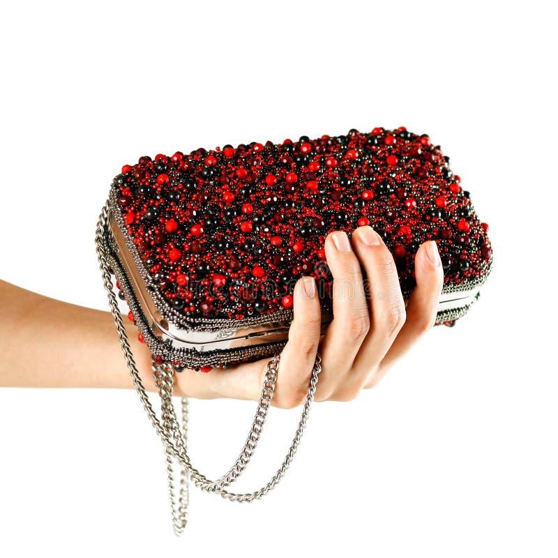 A mão mantém uma bolsa fêmea vermelha pequena coberta com as pedras embreagem fotografia de stock royalty free