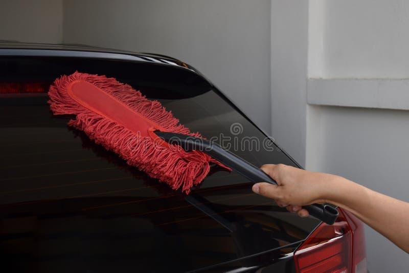 Mão masculina asiática aproximadamente 40 anos de terra arrendada velha uma escova vermelha da poeira Limpe o carro preto imagens de stock