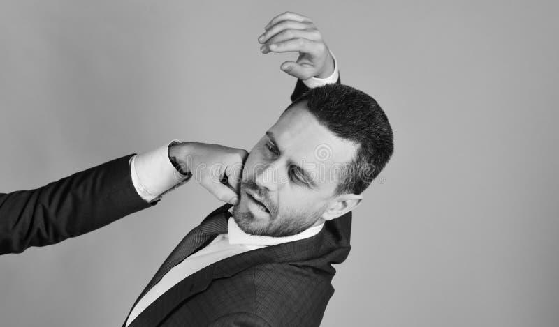 A mão masculina bate o homem com a barba na cara no fundo vermelho Conceito da rivalidade do negócio Homem de negócios com cara d fotografia de stock
