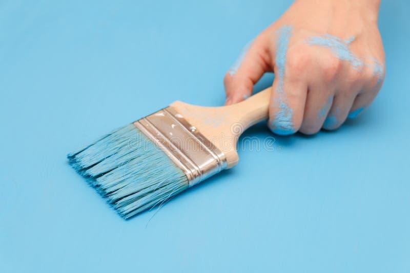 Mão masculina coberta na pintura, guardando uma escova de pintura em uma superfície de madeira do fundo fotografia de stock royalty free
