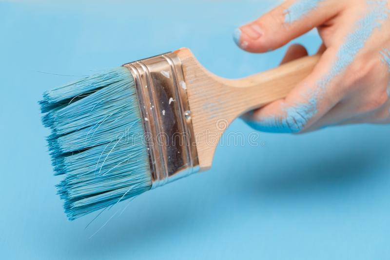 Mão masculina coberta na pintura, guardando uma escova de pintura em uma superfície de madeira do fundo, pintada com a pintura az foto de stock royalty free