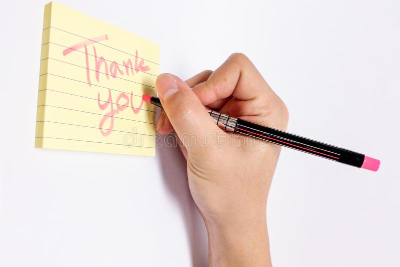 A mão masculina com escrita fluorescente cor-de-rosa do marcador agradece-lhe exprimir no caderno pegajoso amarelo com linha foto de stock