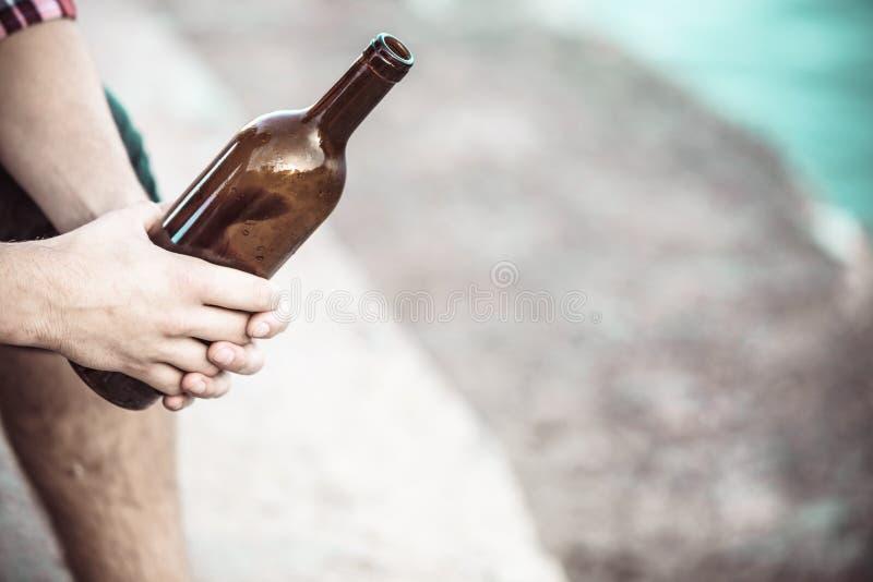 Mão masculina com a garrafa de vinho exterior imagens de stock