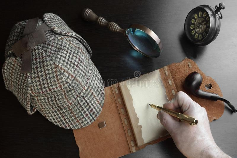 Mão masculina com pena, Notebok aberto, chapéu do Deerstalker fotos de stock royalty free