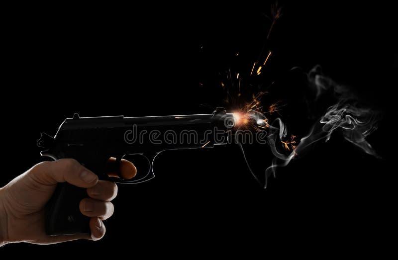Mão masculina com a pistola no fundo escuro fotografia de stock royalty free