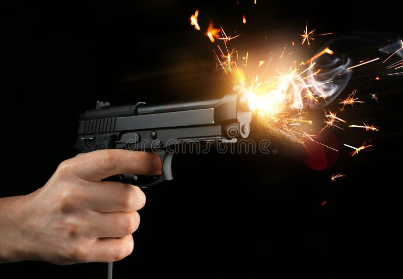 Mão masculina com a pistola no fundo escuro fotos de stock