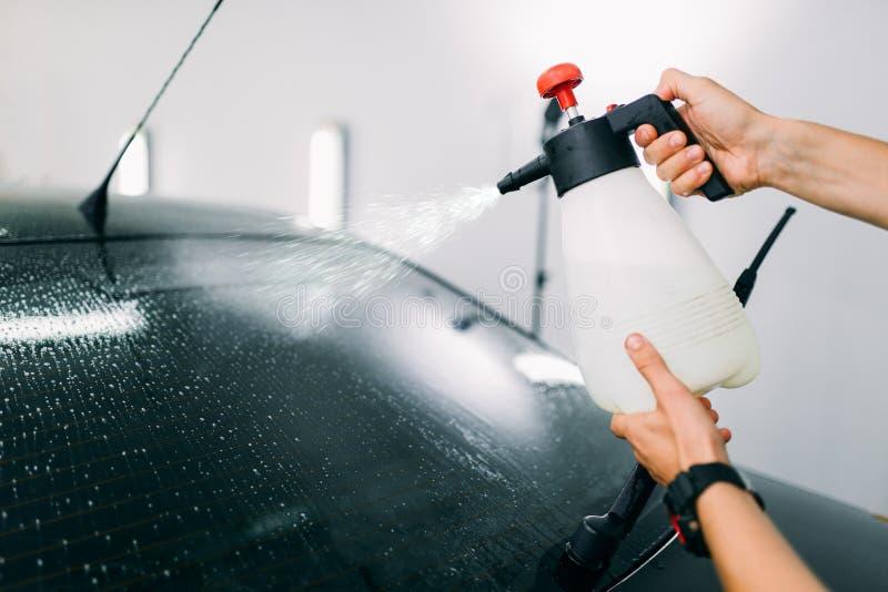 Mão masculina com pulverizador, a instalação do matiz da janela de carro imagem de stock