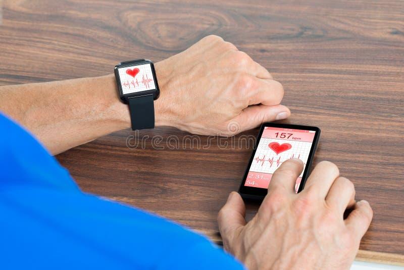 Mão masculina com smartwatch e telefone celular fotografia de stock royalty free