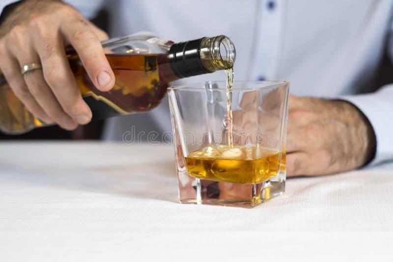 A mão masculina derrama o uísque de uma garrafa em um vidro do gelo fotos de stock