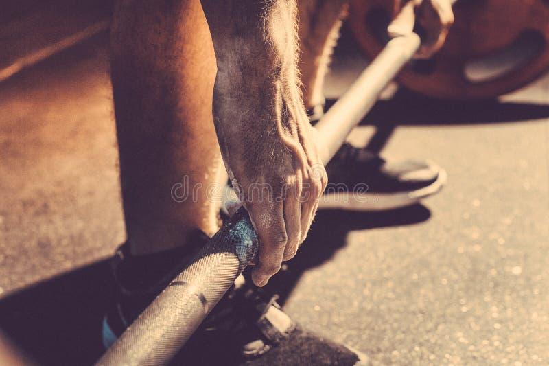 Mão masculina do powerlifter no talco preparação antes de levantar peso Imagem tonificada imagens de stock royalty free