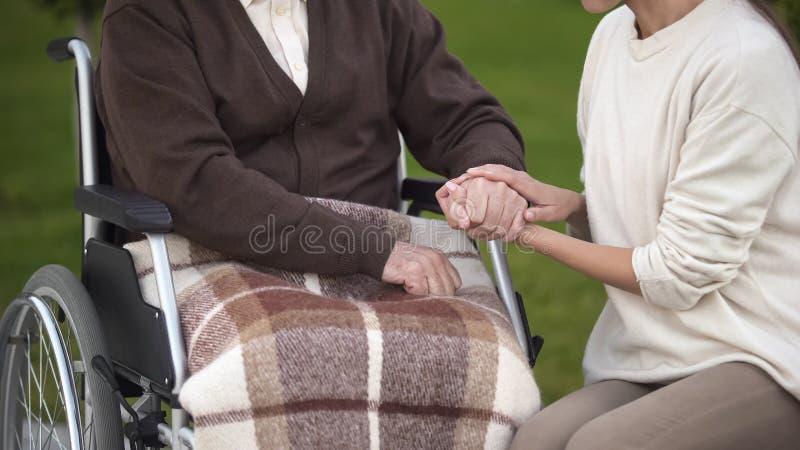 Mão masculina envelhecida guardando fêmea, avô de visita no hospital, lar de idosos foto de stock