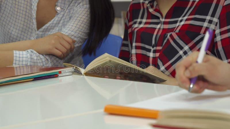 A mão masculina escreve no caderno na biblioteca fotos de stock royalty free