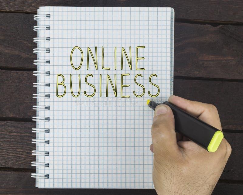 A mão masculina está escrevendo o negócio em linha em um bloco de notas fotografia de stock royalty free