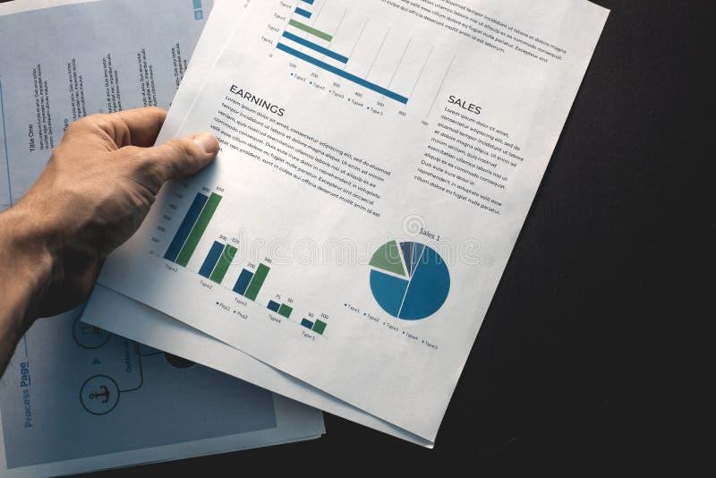 A mão masculina guarda gráficos e texto em uma folha de papel branca imagens de stock