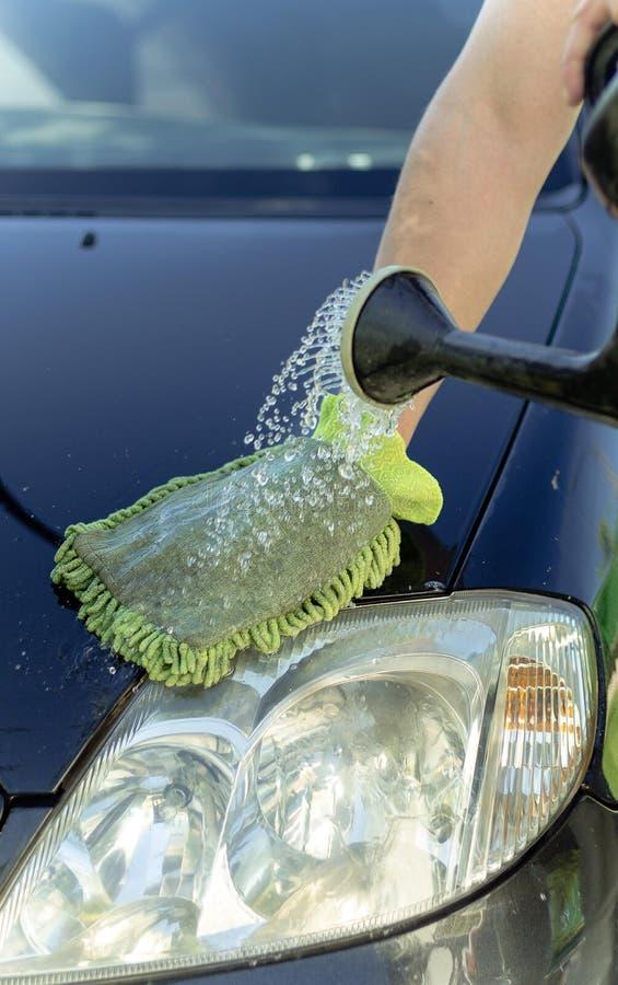 A mão masculina lava o carro com uma mangueira imagem de stock