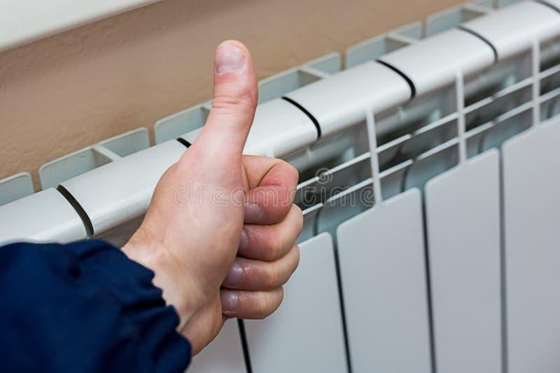 A mão masculina mostra o polegar acima no fundo de um radiador bimetálico de alumínio do aquecimento o conceito do bom trabalho fotos de stock