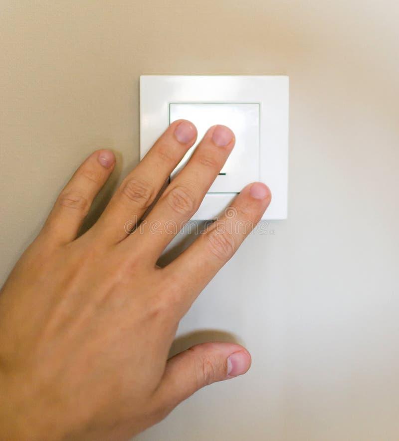 A mão masculina pressiona o interruptor e gerencie sobre a luz fotografia de stock